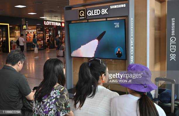 People watch a television news screen showing a file footage of North Korea's missile launch, at a railway station in Seoul on August 6, 2019. -...