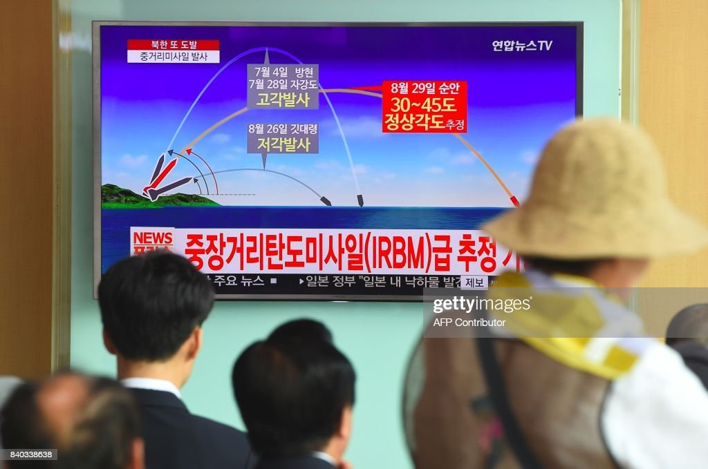 People watch a television news screen showing a graphic of a North Korean missile launch, at a railway station in Seoul on August 29, 2017. Nuclear-armed North Korea fired a ballistic missile over Japan and into the Pacific Ocean on August 29 in a major escalation by Pyongyang amid tensions over its weapons ambitions. / AFP PHOTO / JUNG Yeon-Je