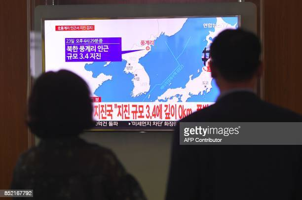 People watch a television news screen showing a map of the epicenter of an earthquake in North Korea at a railway station in Seoul on September 23...
