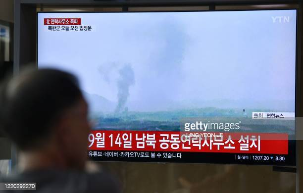 TOPSHOT People watch a television news screen showing an explosion of an interKorean liaison office in North Korea's Kaesong Industrial Complex at a...
