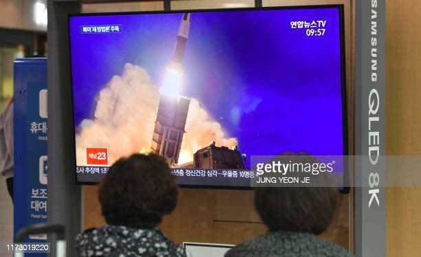 People watch a television news screen showing file footage of a North Korean missile launch, at a railway station in Seoul on October 2, 2019. -...