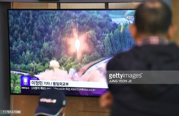 People watch a television news screen showing file footage of a North Korean missile launch, at a railway station in Seoul on October 31, 2019. -...