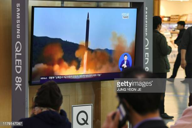 People watch a television news screen showing file footage of a North Korean missile launch at a railway station in Seoul on October 31 2019 North...
