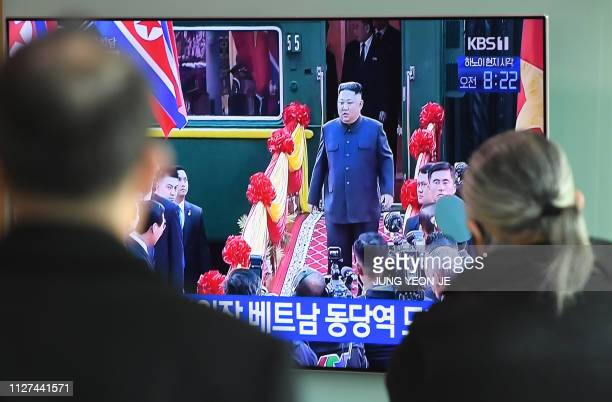 People watch a television news screen showing live footage of the arrival of North Korean leader Kim Jong Un at the Dong Dang railway station in...
