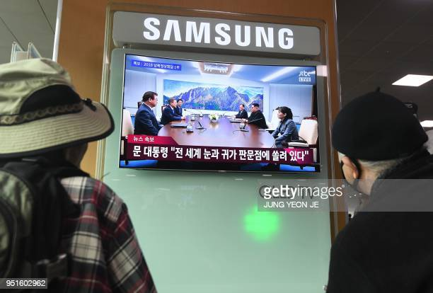 People watch a television news screen showing live footage of the InterKorean summit between South Korean President Moon Jaein and North Korean...