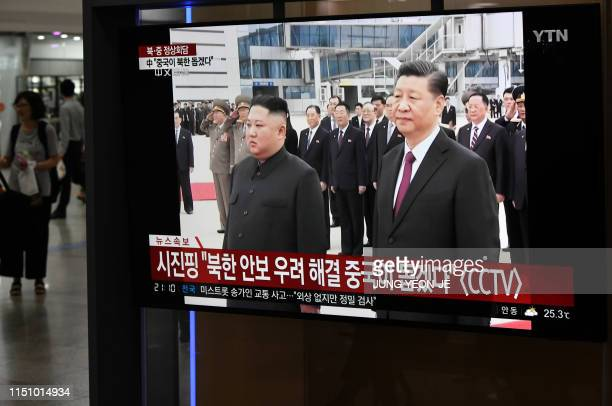 People watch a television news screen showing North Korean leader Kim Jong Un welcoming Chinese President Xi Jinping at Pyongyang airport at Seoul...