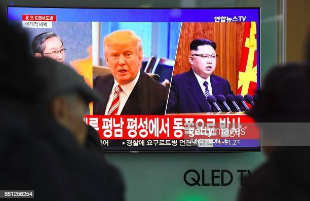 TOPSHOT People watch a television news screen showing pictures of US President Donald Trump and North Korean leader Kim JongUn at a railway station...