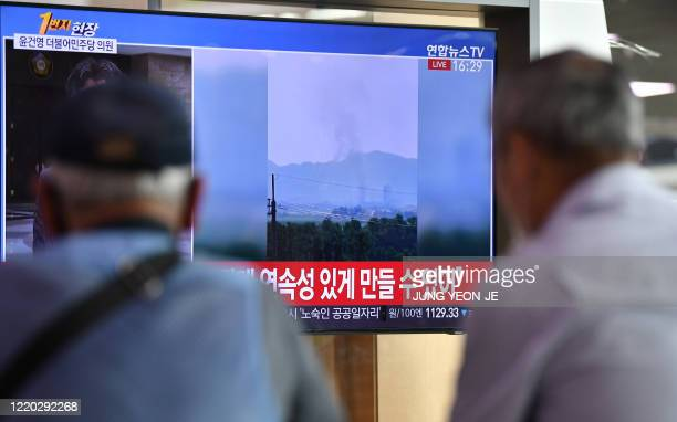 People watch a television news screen showing smoke from the explosion of an inter-Korean liaison office in North Korea's Kaesong Industrial Complex,...