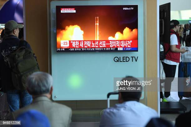 TOPSHOT People watch a television news showing a file footage of North Korean missile launch at a railway station in Seoul on April 21 2018 North...