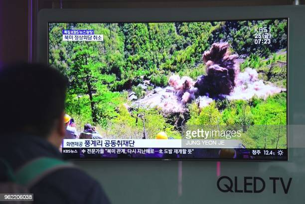 TOPSHOT People watch a television news showing a picture of the dismantling of North Korea's Punggyeri nuclear test site at a railway station in...