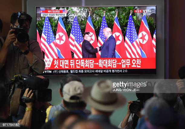 People watch a television screen showing live footage of the summit between US President Donald Trump and North Korean leader Kim Jong Un in...