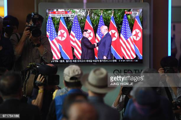 TOPSHOT People watch a television screen showing live footage of the summit between US President Donald Trump and North Korean leader Kim Jong Un in...