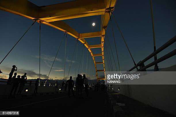 TOPSHOT People watch a total total solar eclipse in Palu Central Sulawesi on March 9 2016 A total solar eclipse swept across the vast Indonesian...