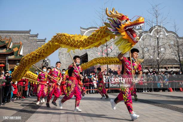 People watch a traditional dragon dance performance during the second day of Spring Festival in Han Kou Li on February 13, 2021 in Wuhan, Hubei...