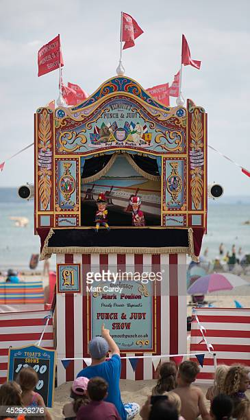 People watch a traditional Punch and Judy show on the beach as they enjoy the warm weather on the seafront on July 30 2014 in Weymouth England...