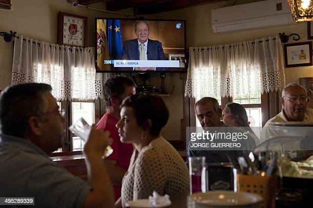 People watch a TV broadcast of Spain's King Juan Carlos addressing the nation following his abdiction in Ronda on June 2 2014 Spanish King Juan...
