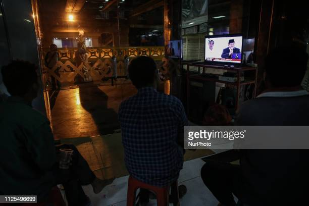 People watch a TV screen showing a live broadcast of Indonesia's presidential candidate Prabowo Subianto speaks during a debate with his opponent...