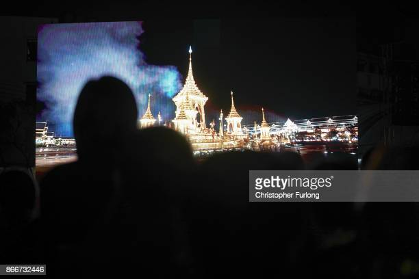 People watch a video screen of cannon smoke next to the Royal Crematorium during the funeral of the late Thai King Bhumibol Adulyadej on October 26...