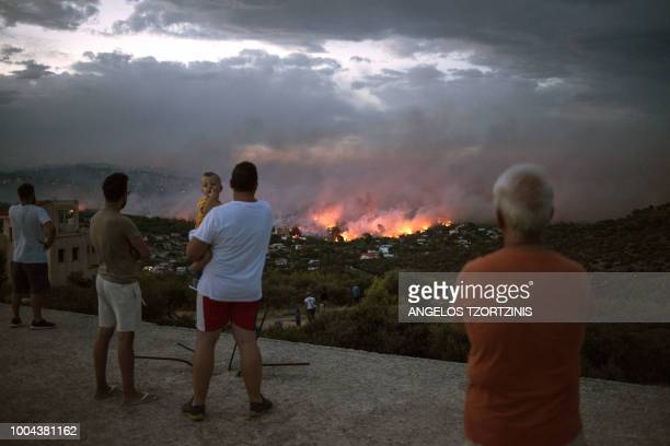 TOPSHOT People watch a wildfire in the town of Rafina near Athens on July 23 2018 At least 20 people have died and more have been injured as wild...