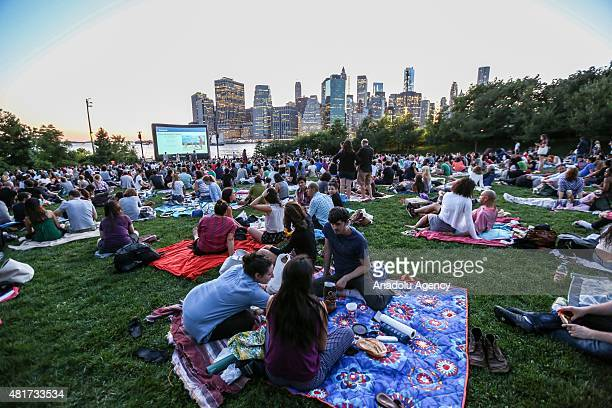 People watch an outdoor screening of the film 'Attack the Block' at Brooklyn Bridge Park on July 23, 2015 in New York City, New York.
