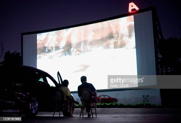 People watch an outdoor screening of 'The Weight of Water' as part of the Beijing Film Festival, at a drive-in cinema in Beijing on August 24, 2020.