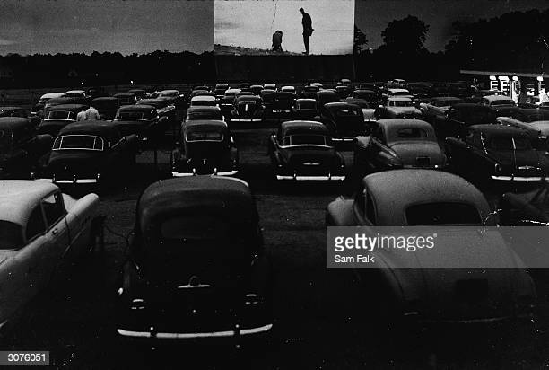 People watch an unidentified movie from inside their cars at a drivein on Long Island New York 1950s