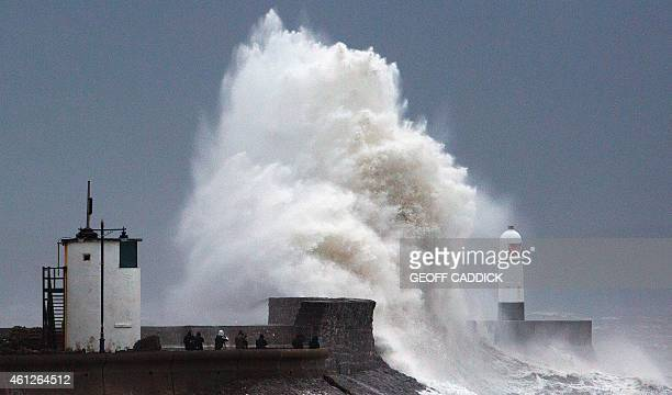 People watch and photograph as large waves batter the harbour wall and lighthouse at Porthcawl in south Wales on January 10 2015 after a second...