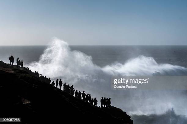 People watch and take photos of the waves and surfers during a surf session at Praia do Norte on January 17 2018 in Nazare Portugal