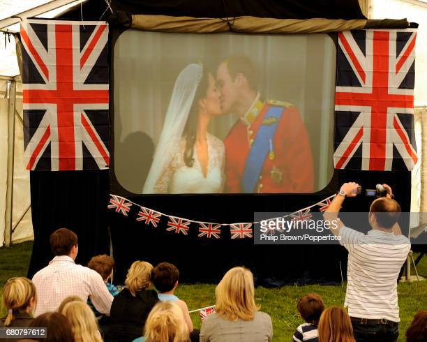 People watch as a big screen in a tent shows the first kiss at a gathering in Bucklebury near Reading on the day that Kate Middleton married Britains...