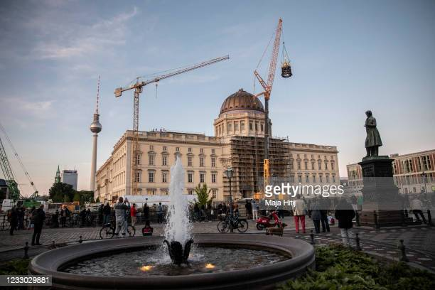 People watch as a crane lifts the newly-finished gold-covered cupola and cross onto the dome of the rebuilt Berlin City Palace on May 29, 2020 in...