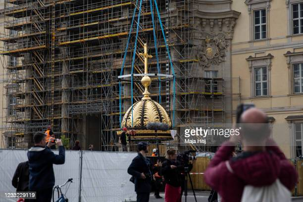 People watch as a crane lowers the newly-finished gold-covered cupola and cross onto a supporting structure of angels prior to hoisting the combined...