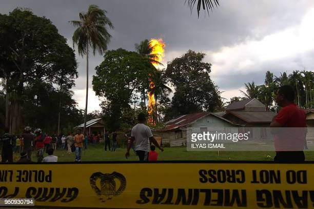 People watch as a fire burns at an oil well in Peureulak Indonesia's Aceh province on April 25 2018 At least 10 people have been killed and dozens...