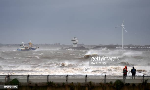 People watch as a fishing boat navigates stormy seas on its way into the River Mersey in New Brighton north west England on February 9 as Storm Ciara...