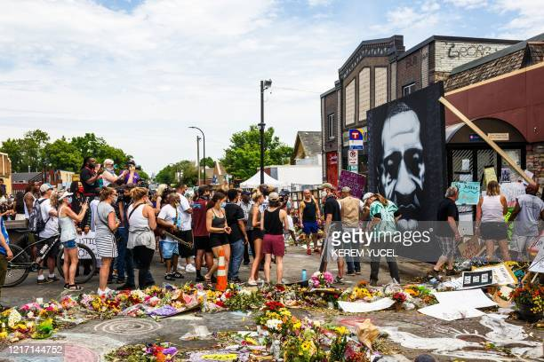 People watch as a photo of George Floyd is mounted on the side of the bus station at the location of his death on June 2 2020 in Minneapolis...