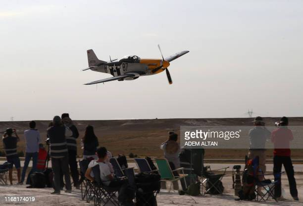 People watch as a plane performs during the Sivrihisar Airshow in Sivrihisar district of Eskisehir on September 14 2019