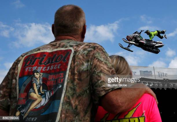 People watch as a Snowmobile glides through the air part of a Freestyle Motocross Demo held for fans before the Bass Pro Shops NRA Night Race...