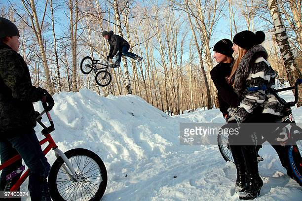 People watch as a teenagee jumps with a BMX bike from a snowy bank in the town of Berezniki Perm region on February 28 2010 AFP PHOTO / EVGENY SAMARIN