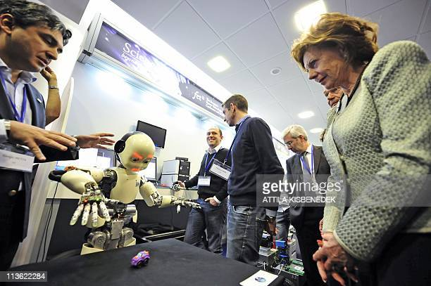 People watch as a toy car is placed in front of a pattern recognition and movement coordination multirobot during the FET11 The European Future...