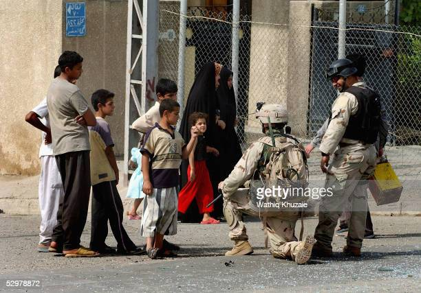 People watch as a US soldier and an Iraqi translator secure the scene of a suicide car bomb explosion which failed to hit a US military convoy May 25...