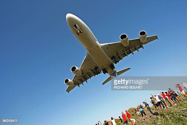 People watch as an Airbus A380 flies over the Indian ocean island of La Réunion during an exhibition flight before landing at the RolandGarros...