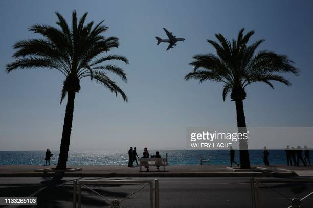 TOPSHOT People watch as an Emirates Airbus A380 approaches the airport of the French riviera city of Nice on March 28 2019