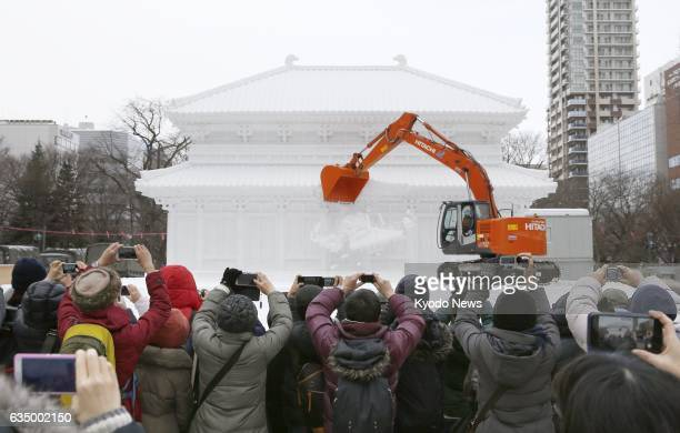 People watch as an excavator demolishes a snow sculpture of the Central Golden Hall of Kofukuji a renowned temple in the western Japan city of Nara...