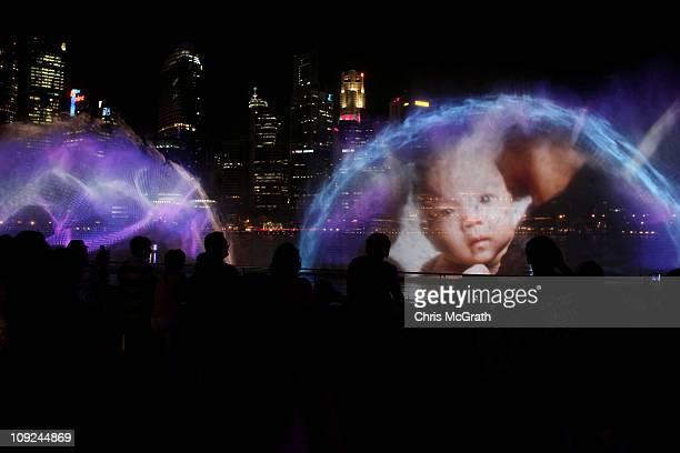 People watch as an image of a baby is projected through water during Wonder Full a light and water show to mark the official grand opening of Marina...