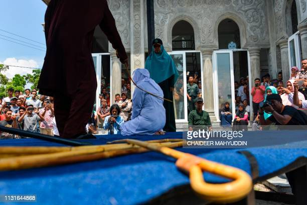 TOPSHOT People watch as an Indonesian woman is whipped by a member of the Sharia police in public in Banda Aceh on March 20 2019 A group of unmarried...
