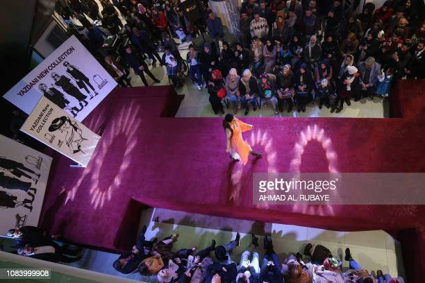 People watch as an Iranian model as she presents a creation by two Iranian female fashion designers during a show at a shopping mall in the Iraqi...