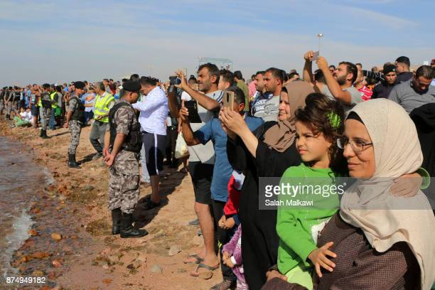 People watch as Aqaba authorities in Jordan sink the body of a military transport C130 Hercules plane which is out of service and was donated by the...