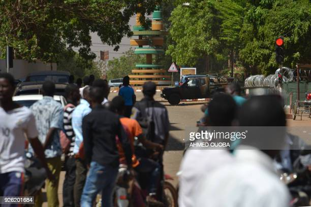 People watch as black smoke rises as the capital of Burkina Faso came under multiple attacks on March 2 targeting the French embassy, the French...