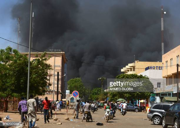 TOPSHOT People watch as black smoke rises as the capital of Burkina Faso came under multiple attacks on March 2 targeting the French embassy the...