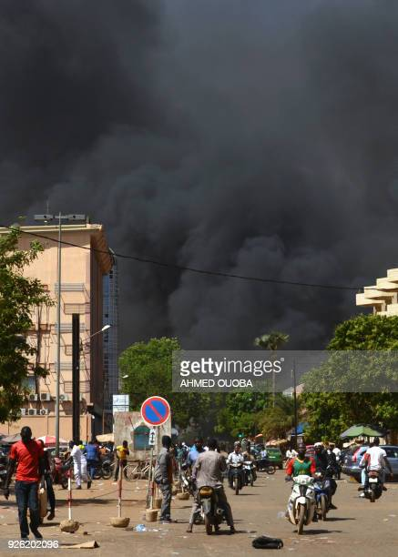 People watch as black smoke rises as the capital of Burkina Faso came under multiple attacks on March 2 targeting the French embassy the French...