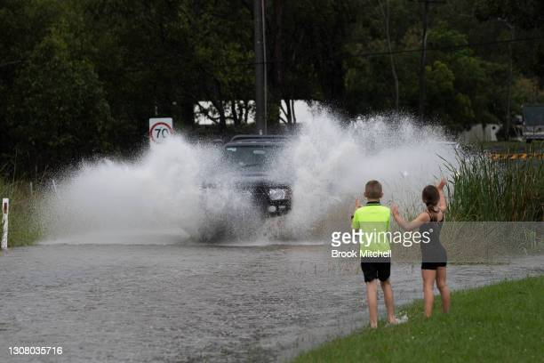 People watch as cars drive through flood waters in Pitt Town on March 20, 2021 in Pitt Town, Australia. Heavy rain and flooding has trigger...